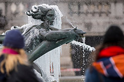 © Licensed to London News Pictures. 09/02/2021. LONDON, UK. Women view one of the ice covered frozen fountains in Trafalgar Square during light snow flurries as the cold weather brought on by Storm Darcy continues.  Photo credit: Stephen Chung/LNP