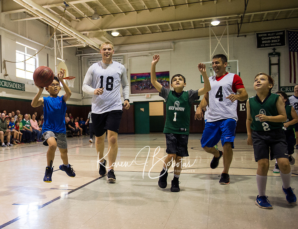 A battle on the court between Holy Trinity Students and the Laconia Police Dept on Saturday morning at Holy Trinity School.  (l-r) Ben Valles, Tyler Rouse, Mark Langlitz, Tony Horan and Levi Fernandez.  (Karen Bobotas/for the Laconia Daily Sun)
