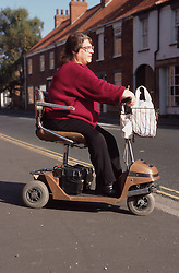 Woman with disability riding electric scooter,
