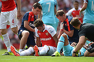 Olivier Giroud of Arsenal receives treatment after being injured after clashng heads  with James Tomkins of West Ham United via a leap for the ball. Barclays Premier League, Arsenal v West Ham Utd at the Emirates Stadium in London on Sunday 9th August 2015.<br /> pic by John Patrick Fletcher, Andrew Orchard sports photography.