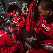 Leg 3, Cape Town to Melbourne, day 12, Blair Tuke, Pablo Arrarte and Louis Sinclair squeezing in breakfast in between gybes on board MAPFRE. Photo by Jen Edney/Volvo Ocean Race. 20 December, 2017.