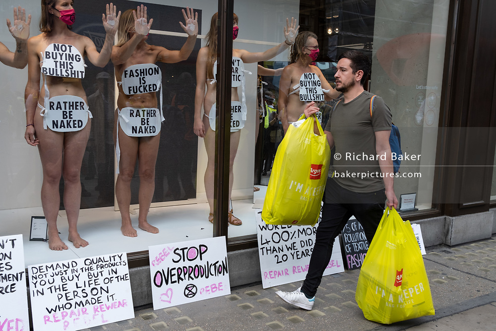 A shopper walks past supporters of environmental and Climate Change group Extinction rebellion, protesting against the ehtics of the fashion industry by glueing their hands to the window of H&M on Oxford Street, on 9th September 2020, in London. XR say that the fashion industry produces around 10% of all humanity's carbon emissions, more than all international flights and maritime shipping combined and that over 800,000 tonnes of discarded textile waste annually in the UK.