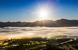 © Licensed to London News Pictures. 20/09/2021. Keswick UK. The 98% Waxing Gibbous moon lights up the night sky in the early hours of this morning over the fog covered town of Keswick in Cumbria. Photo credit: Andrew McCaren/LNP