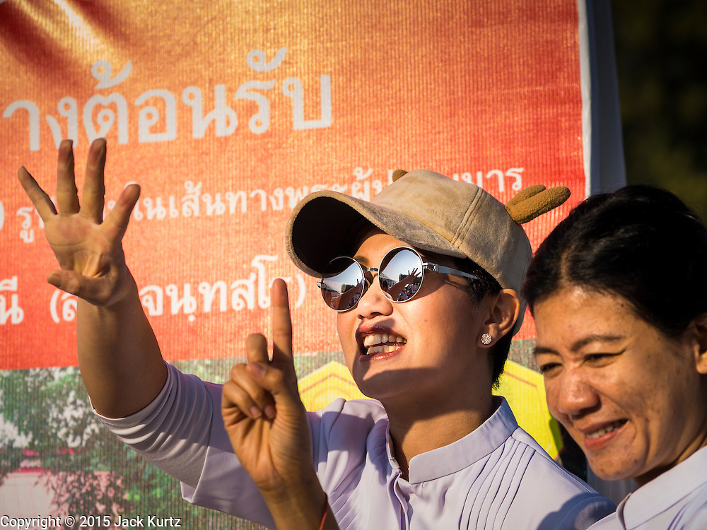"""02 JANUARY 2015 - KHLONG LUANG, PATHUM THANI, THAILAND: A woman cheers at Wat Phra Dhammakaya at the start of the 4th annual Dhammachai Dhutanaga (a dhutanga is a """"wandering"""" and translated as pilgrimage). More than 1,100 monks are participating in a 450 kilometer (280 miles) long pilgrimage, which is going through six provinces in central Thailand. The purpose of the pilgrimage is to pay homage to the Buddha, preserve Buddhist culture, welcome the new year, and """"develop virtuous Buddhist youth leaders."""" Wat Phra Dhammakaya is the largest Buddhist temple in Thailand and the center of the Dhammakaya movement, a Buddhist sect founded in the 1970s.   PHOTO BY JACK KURTZ"""