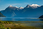 Rounded snowy peaks rise over a green marsh in fjord-like Lago Yelcho, near Puerto Ramirez, Palena Province, Chile, Andes mountains, Patagonia, South America.