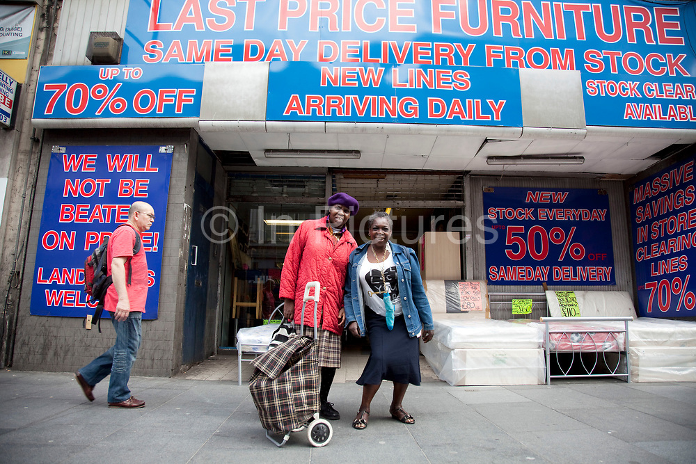 Two women pose outside a cut price furniture store on Brixton Road, a multicultural area in South London. Brixton is a district in south London, England, in the London Borough of Lambeth. The area is identified in the London Plan as one of 35 major centres in Greater London. Brixton is predominantly residential with a prominent street market and substantial retail sector. It is a multiethnic community, with around 24 percent of Brixton's population being of African and Caribbean descent, giving rise to Brixton as the unofficial capital of the British African-Caribbean community.