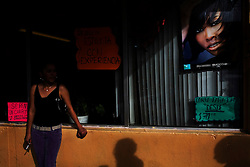 A woman smokes a cigarette outside a hair salon in downtown Nogales.