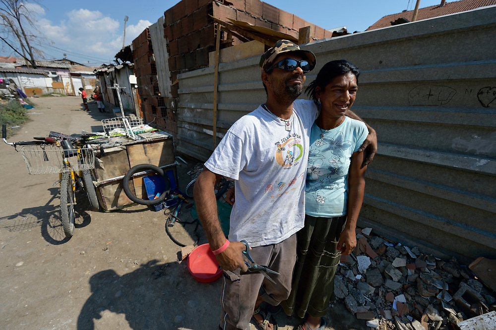 A man and woman pose for a photographer on a street in Suto Orizari, Macedonia. The mostly Roma community, located just outside Skopje, is Europe's largest Roma settlement. .
