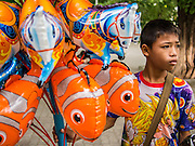 """22 JULY 2013 - PHRA PHUTTHABAT, THAILAND:  A boy sells inflatable toys during the Tak Bat Dok Mai at Wat Phra Phutthabat in Saraburi province of Thailand, Monday, July 22. Wat Phra Phutthabat is famous for the way it marks the beginning of Vassa, the three-month annual retreat observed by Theravada monks and nuns. The temple is highly revered in Thailand because it houses a footstep of the Buddha. On the first day of Vassa (or Buddhist Lent) people come to the temple to """"make merit"""" and present the monks there with dancing lady ginger flowers, which only bloom in the weeks leading up Vassa. They also present monks with candles and wash their feet. During Vassa, monks and nuns remain inside monasteries and temple grounds, devoting their time to intensive meditation and study. Laypeople support the monastic sangha by bringing food, candles and other offerings to temples. Laypeople also often observe Vassa by giving up something, such as smoking or eating meat. For this reason, westerners sometimes call Vassa the """"Buddhist Lent.""""    PHOTO BY JACK KURTZ"""