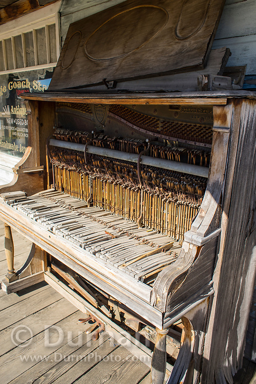 An old piano on the porch of an old strucutre in the remnants of an old town in Shaniko, Oregon.