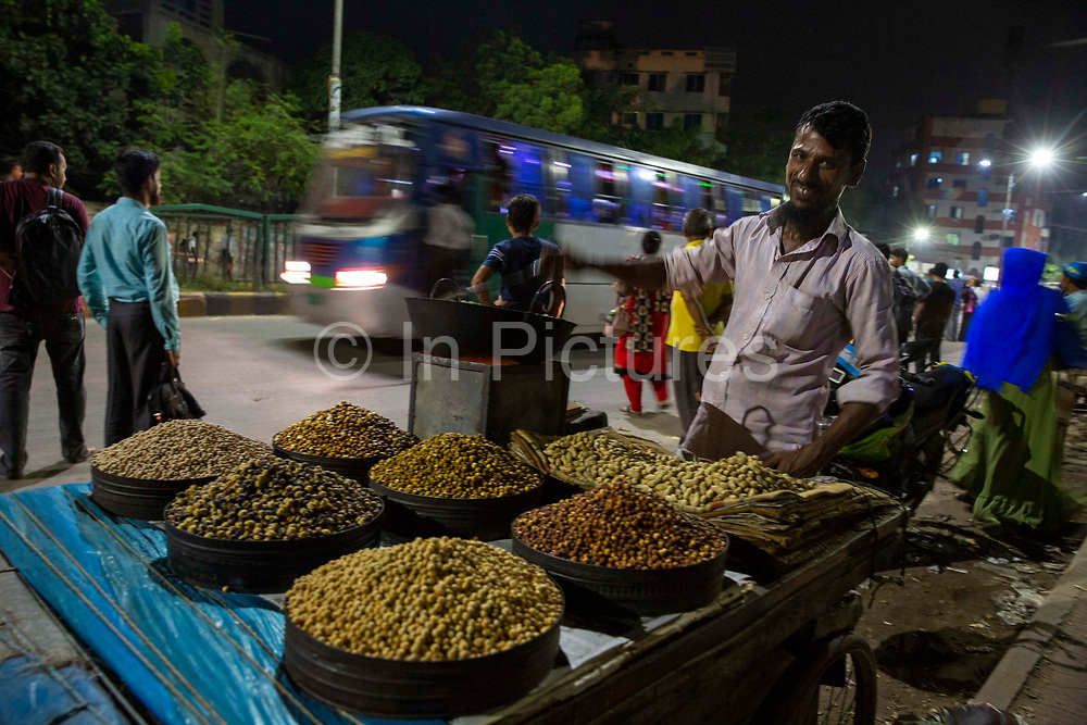 A man selling fried nuts and corn from his market stall at night next to road in the Tejgaon railway district on the 23rd of September 2018 in Dhaka, Bangladesh.
