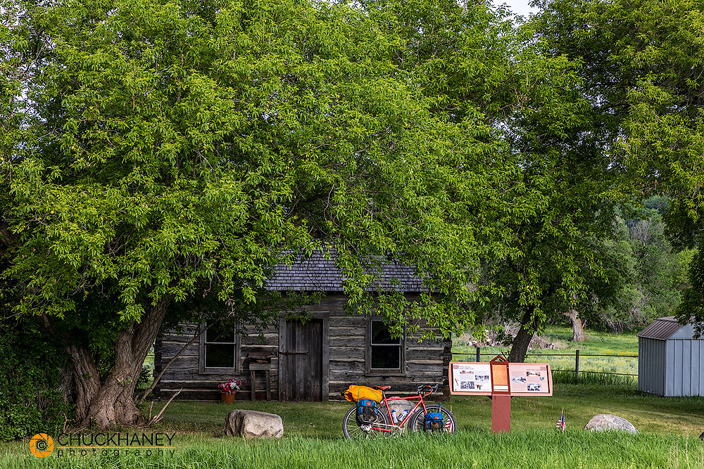 Bicycle touring along the Sheyenne Scenic Byway with Historic Slattum Homestead Cabin in southeastern North Dakota, USA