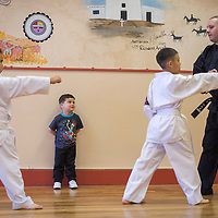 Azazel Herrera watches his father, Jerry Herrera Jr., teach karate class at the Catholic Indian Charities in Gallup Wednesday.
