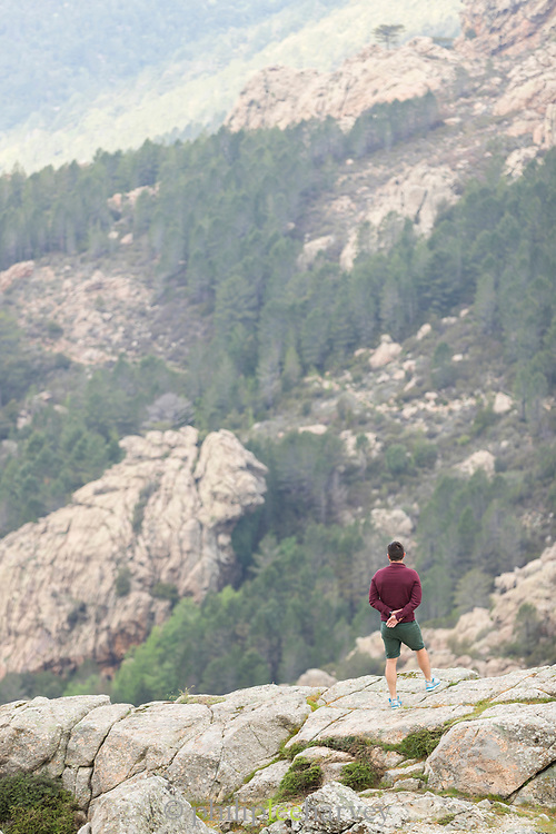 Hiker looking at view in mountains, Col de Bavella, Corsica, France