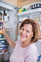 Portrait of senior woman infront of open refrigerator, smiling