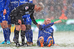 Everton's Wayne Rooney is helped up by referee Martin Atkinson during the Premier League match at the bet365 Stadium, Stoke.