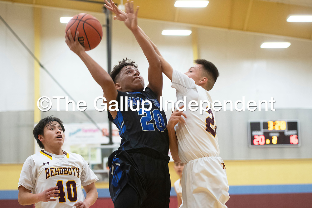 Navajo Pine Warrior Dempsey Lincoln (20) drives to the basket as Rehoboth Lynx Preston Hawthorne (24) defends Tuesday evening in Rehoboth.