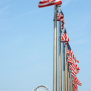 A row of flags, with a giant ferris wheel in the background, at National Harbor on the waterfront of the Potomac in Maryland, near Washington DC.