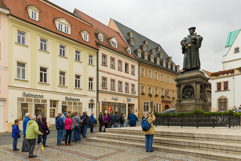 A statue of Martin Luther stands above visitors in the town square of Eisleben, Germany.