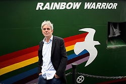 © Licensed to London News Pictures. 08/11/2011. London, UK. John Sauven, the Executive Director on Greenpeace next to the environmental organisation's  flagship, Rainbow Warrior in South Quay in London's Docklands today 8th November 2011, after making her maiden voyage from Amsterdam. It is the first Greenpeace ship to have been specifically built, the previous two being refits. Photo credit : Stephen Simpson/LNP