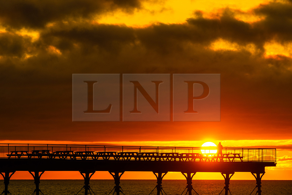 ©Licensed to London News Pictures. 16/09/2019 Aberystwyth UK. <br /> A man standing on Aberystwyth's Victorian seaside pier is silhouetted as he watches the last rays of the suns as it sets over Cardigan Bay, on a glorious mid autumn evening, The week ahead is expected to be warm and settled with a high pressure system dominating the weather in the southern parts of the UK. Photo credit Keith Morris/LNP