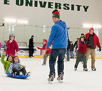 """Santa's Helper Brad Wilkinson pulls Maisy Mure and Theadora Stark in their """"sleigh"""" around Plymouth Ice Arena's Skate with Santa event Sunday afternoon.  (Karen Bobotas/for the Laconia Daily Sun)"""