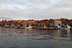 Lungomare di Taranto con pescherecci attraccati alla banchina del porticciolo.