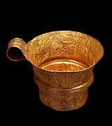 Gold cup with repose representation of dolphins within a seascape. Mycenaean Greece was a cultural period of Bronze Age Greece taking its name from the archaeological site of Mycenae