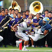 San Benito's Juan Salas runs by a diving McAllen Memorial's Joey Delgado as the San Benito band watches from the sideline during the second quarter of their game at Veterans Memorial Stadium in McAllen.<br /> Nathan Lambrecht/The Monitor