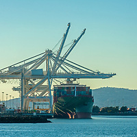 Giant cranes unload containers from a ship anchored in Long Beach Harbor, California.