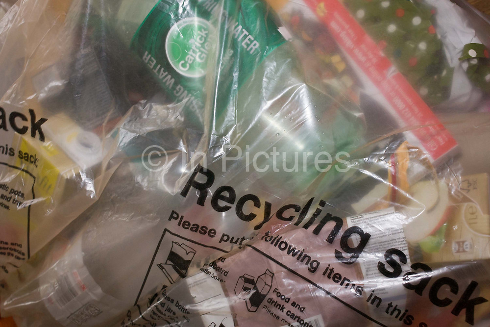 The contents of a transparent plastic recycling sack provided by Lambeth council. Bagged up and ready for collection, the sack is filled with the detritus and domestic rubbish from household waste - products with recyclable packaging.