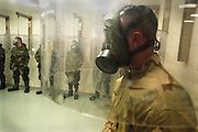 18 Dec 2002, Missouri, USA --- After training, the last test of the gas mask is conducted before exposure to live Sarin & VX nerve agents. To test the masks, Navy, Army and Marine troops are placed under a plastic housing. Then, they are exposed to banana oil and/or other caustic agents. If subject either smells the oil or reacts to the caustic agent, the gas mask is not working and the trainee is pulled out of the next phase, which is lethal exposure to nerve agents. --- Photo by Leif Skoogfors/Corbis | Location: Fort Leonard Wood, Missouri, United States.  --- Image by © Leif Skoogfors