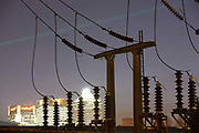 As evening light fades, bright light from the electricity-hungry Canary Wharf docklands development is supplied by the voltage from electricity cables and supporting struts at West Ham sub-station, Canning Town, London England. A network of 110 miles of cables have stretched across 542 'L6' pylons across England's Kent countryside, from the coal-fired power station at Dungeness to this location, carrying 40,000 Volts along this network of aluminium cables to power some of London's high supply demands. Insatiable appetites for energy means electricity is now an expensive comodity after climbing oil prices doubled electricity utility bills for some domestic users.