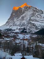 A true alpenglow hits the Wetterhorn above a sleepy Swiss village.