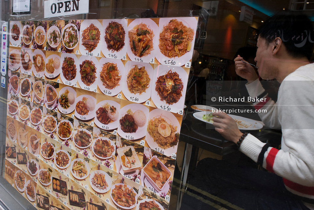 Near a menu of dishes, a customer eats a lunchtime Chinese meal in the window of a Soho eaterie.
