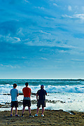 Young men looking out to sea watching the waves breaking, Doolin, County Clare, West Coast of Ireland