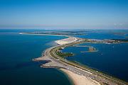 Nederland, Zuid-Holland, Ouddorp, 12-06-2009; de Brouwersdam, onderdeel van de Deltawerken (1971), tussen Goeree en Schouwen (aan de horizon, provincie Zeeland). Links het Grevelingenmeer en in het midden Middelplaat met recreatiecentrum en vakantiepark Port Zelande. In de verte de Oosterschelde, rechts de Noordzee. <br /> Na het afsluiten van de zeearm Grevelingen zijn gaandeweg ernstige milieuproblemen in het nieuwe zoetwater ontstaan. De reeds in 1978 extra gebouwde doorlaatsluis, de Brouwerssluis (bij de uitstulping), heeft onvoldoende verlichting gebracht, er zijn nu plannen om een opening in de dam te maken om zo het getij deels terug te laten keren.<br /> Brouwers dam between the islands Schouwen and Goeree (at the horizon). To the right Grevelingen (confluent Meuse and Rhine), Northsea to the left. At the horizon another sea arm of Meuse and Rhine.<br /> luchtfoto (toeslag op standaard tarieven);<br /> aerial photo (additional fee required);<br /> copyright foto/photo Siebe Swart.