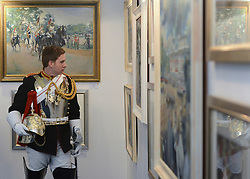 © Licensed to London News Pictures. 20/04/2012. London, UK . A soldier looks around the exhibition. A Preview of the Household Cavalrys 'The Best of British' art exhibition. Soldiers walk around the artwork as they prepare to mount duties at Horse Guards Parade. The Queen's Life Guard are inspected before they depart the Barracks for the daily Guard change at 1100. The exhibition runs between 23 - 26 April. Hyde Park Barracks, Ceremonial Gate, South Carriage Drive, London, SW7 1SE. Photo credit : Stephen Simpson/LNP