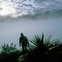 Cordillera Vilcabamba, Andes Mountains, Peru. Ben Wiltsie atop Cerro Victoria, an Inca ceremonial site, on a foggy dawn below Nevado Sacsarayoc.