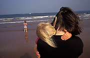 As an older daughter plays in the surf, a young girl hugs her mother while on holiday in the southern English seaside resort of Paignton, on 19th July 1993, in Paignton, England.
