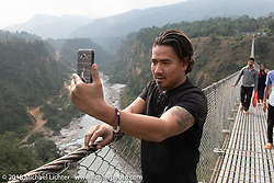A young Nepali man takes a selfie on the Kusma Gyadi Bridge, the tallest (443') and one of the longest (1,128') suspension bridges in the country that cut a hike of many hours to just a few minutes. Day-7 of our Himalayan Heroes adventure riding from Tatopani to Pokhara, Nepal. Monday, November 12, 2018. Photography ©2018 Michael Lichter.