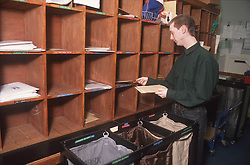 Postal worker sorting letters in mail room,