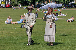 Licensed to London News Pictures. 14/06/2021. London, UK. Ian Crichton <br /> and JJ Bannister, Steam Punk enthusiasts from Surrey cool off in the sunshine the old fashioned way with an ice cream and parasol on Richmond Green, southwest London. Weather experts have forecast warm weather for the next few days for the South East and London with temperatures predicted to hit up to 30c. Photo credit: Alex Lentati/LNP