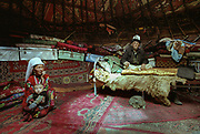 """Abdul Rashid Khan sitting on his bed covered with a wolf skin. He is inside his yurt with his 3rd wife, his youngest son Karzai and his cat. Kara Jelgha (""""black valley"""") summer camp. The campment of Abdul Rashid Khan, the king of the Kyrgyz.<br /> <br /> Adventure through the Afghan Pamir mountains, among the Afghan Kyrgyz and into Pakistan's Karakoram mountains. July/August 2005. Afghanistan / Pakistan."""