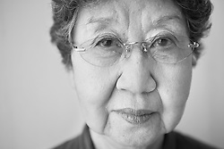 Black and white portrait photograph of Asian senior lady who is frightened and fearful