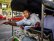 """14 FEBRUARY 2015 - BANGKOK, THAILAND: Student activist Siriwit Serithiwat waves after he was detained and taken away by police in a tuk-tuk (three wheeled taxi) during a protest the military coup. Martial law is still in effect in Thailand and protests against the coup are illegal. Dozens of people gathered in front of the Bangkok Art and Culture Centre in Bangkok Saturday to hand out red roses and copies of George Orwell's """"1984."""" Protestors said they didn't support either Red Shirts or Yellow Shirts but wanted a return of democracy in Thailand. The protest was the largest protest since June 2014, against the military government of General Prayuth Chan-Ocha, who staged the coup against the elected government. Police made several arrests Saturday afternoon but the protest was not violent.      PHOTO BY JACK KURTZ"""