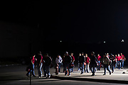 The Iraan High School football team walks to the busses for the final stretch of the trip to Arlington after a light walkthrough in Aledo, Texas on December 14, 2016. (Cooper Neill for The New York Times)