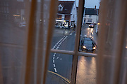An evening viewpoint through a sash window of car headlights and the road junction in a market place of a rural Norfolk town, on 30th June 2021, in Aylsham, Norfolk, England.