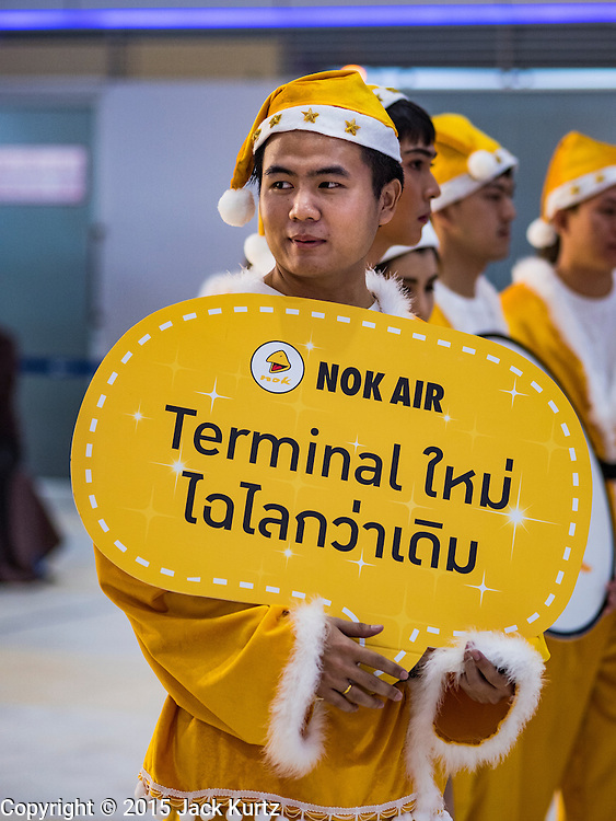"""24 DECEMBER 2015 - BANGKOK, THAILAND: Nok Airlines employees in Santa Claus outfits walk through the new domestic terminal at Don Muang (also spelled Don Mueang) International Airport. The Santa outfits are yellow because that is color Nok uses for its employees' uniforms and planes. The new terminal had its """"soft"""" opening Dec. 24. Don Muang is the airport used by low cost airlines serving Bangkok and is now the largest airport in the world for low cost carriers. In 2014, more than 21million passengers used Don Muang. Don Muang International Airport is the oldest airport in Asia and one of the oldest airports in the world. It started functioning as an airfield in 1914.     PHOTO BY JACK KURTZ"""