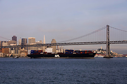 San Francisco, California: Container ship before Bay Bridge and skyline as seen from ferry in early morning. Photo 16-casanf78500. Photo copyright Lee Foster.